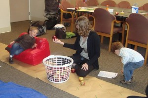 Intern Lindsay Dion engages a toddler with a basket of apples.