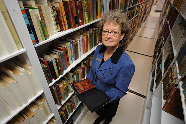 Terri Goldich, curator of the Northeast Children's Literature Collection, holds a copy of 'Black Beauty' while standing in the stacks at the Thomas J. Dodd Research Center. (Peter Morenus/UConn Photo)