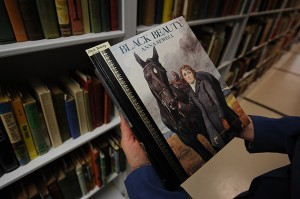 """Terri Goldich holds a copy of """"Black Beauty"""" while standing in the stacks at the Thomas J. Dodd Research Center on Dec. 20, 2011. (Peter Morenus/UConn Photo)"""