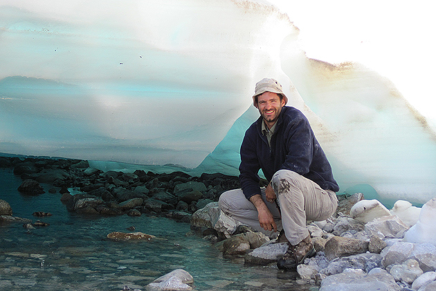 Mark Urban with a sheet of aufeis in Alaska. aufeis in northern Alaska. Aufeis is ice that forms as layers on streams in winter, and is declining as the region becomes warmer. (Photo courtesy of Mark Urban)