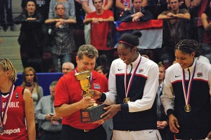 Coach Geno Auriemma shares the trophy with Tina Charles.