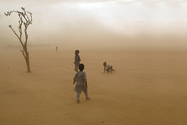 Boys fleeing violence along the border of Darfur and Chad as a sandstorm approaches, 2007