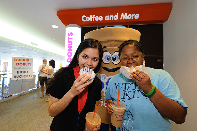 Momina Afrede '14 (CLAS) and Ashly Stovall '14 (CANR), right, each enjoy one of the 1500 blue and white Dunkin Donuts that were given away to celebrate the opening of their new location at the Student Union on March 22, 2012. (Peter Morenus/UConn Photo)