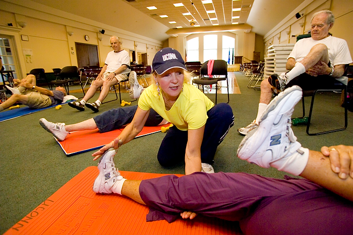 Mary Carroll Root helps participants during a Powerful Aging Exercise class at the Avon Senior Center. (Al Ferreira for UConn Health Center)