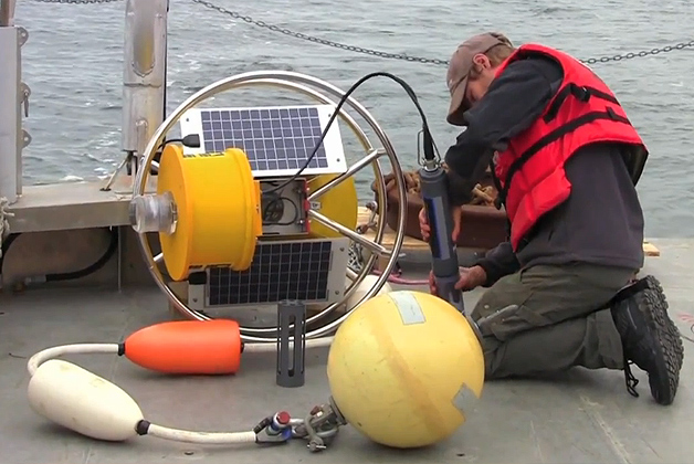 Christian Fox prepares a UConn buoy for deployment out at sea.