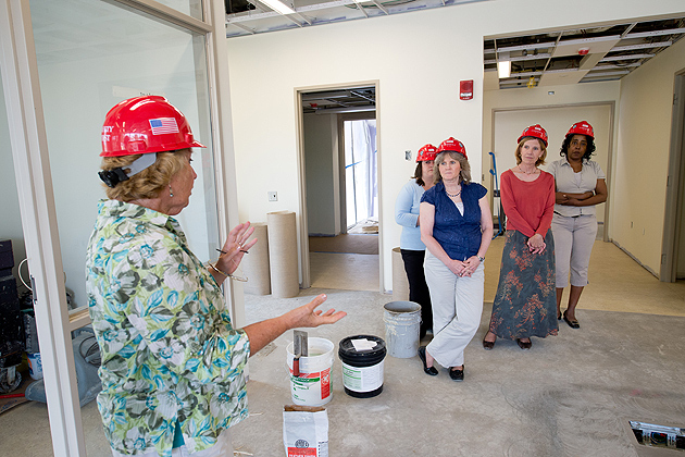 Carol Polifroni, professor of nursing, left, leads professional staff on a tour of the 15,800 square-foot Carolyn Ladd Widmer Wing, under construction at the School of Nursing. The wing will include a reading room, a multi-purpose room, various labs set up as clinical offices, a lab set up as an apartment bedroom to give students experience in at-home caregiving, an auditorium that will serve as a classroom, and a museum of nursing history. Crews expect to start moving equipment and furnishings into the new wing during the last week of July, and employees will transition there in August. (Peter Morenus/UConn Photo)