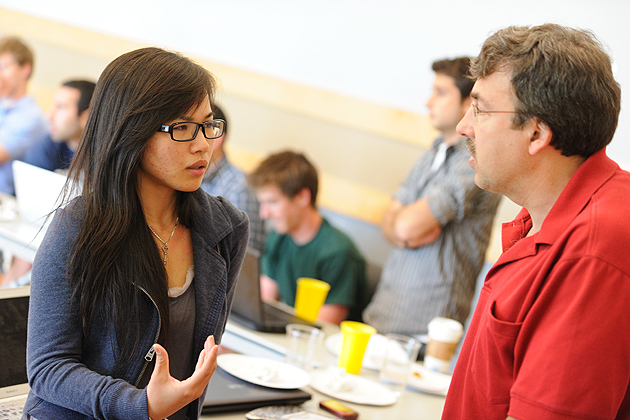 Jolina Li '12 (BUS), left, speaks with UConn's Eric Knight, inQbator coordinator and one of this year's Innovation Quest judges. (Peter Morenus/UConn Photo)