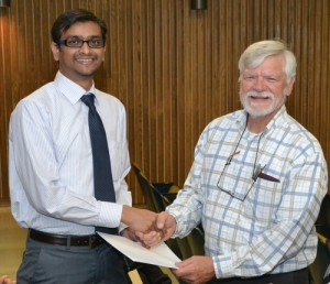 Postdoctoral student Aniket Jadhav (left) accepts an Auxiliary scholarship from Dr. Art Hand. (Chris DeFrancesco/UConn Health Center Photo)