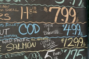 A chalk board lists the prices of fish.