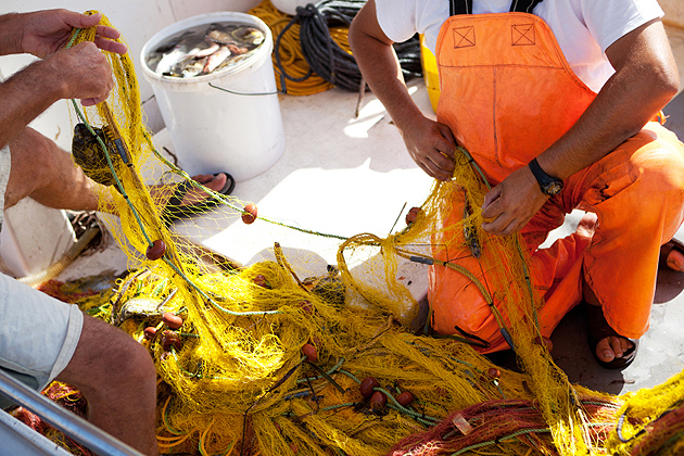 Repairing fishing nets, after fishing the journey.