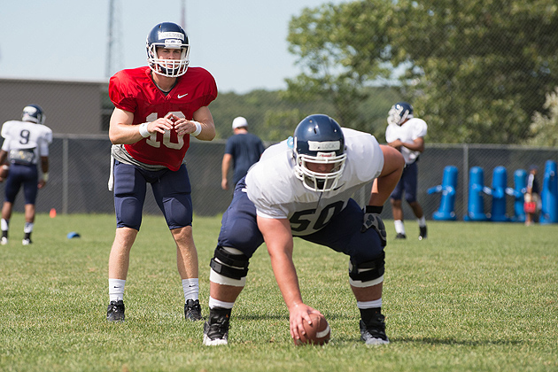 Tyler Bullock '14 snaps the ball to quarterback Chandler Whitmer '14 (CLAS) during the UConn football team's open practice held on the Storrs campus on Aug. 7, 2012. (Peter Morenus/UConn Photo)