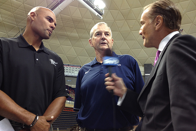 Jim Calhoun, head coach of UConn men's basketball for the past 26 years, speaks with a reporter from SNY after a press conference announcing that he is stepping down. At left is former Husky basketball player Donny Marshall. (Peter Morenus/UConn Photo)