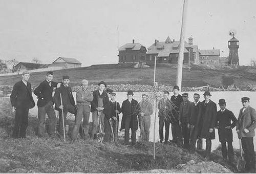 As a departing gift to the college, members of the Class of 1893, the first to graduate after Storrs Agricultural College was designated as Connecticut's land grant institution, plant a willow tree in front of Duck Pond (now Swan Lake). The pole behind them held the line to the only telephone on campus, located in the President's Office in Whitney Hall (seen on left). (University Photograph Collection, Archives & Special Collections)