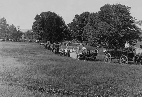 In celebration of Farmers Week 1921, a parade of horse teams and wagons passes a group of observers. Connecticut Agriculture College buildings are visible in the background. (University Photograph Collection, Archives & Special Collections)