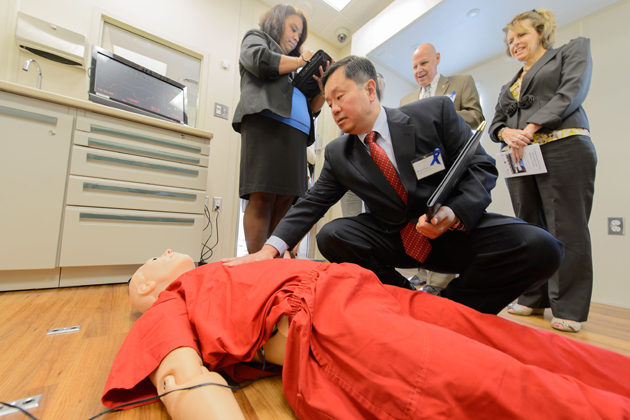 Mun Choi, interim provost, reaches to feel the breathing of a simulated corrections inmate onboard the Mobile Simulation Laboratory. Standing from left are Desiree Diaz, assistant clinical professor of nursing, Leo Arnone, state commissioner of corrections, and Cheryl Cepelak, assistant commissioner of corrections. (Peter Morenus/UConn Photo)