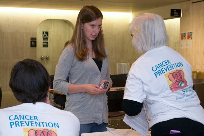 American Cancer Society staffers explain next steps to CPS-3 participant Jen Cyr, who had just submitted her enrollment questionnaire. (Tina Encarnacion/UConn Health Center Photo)