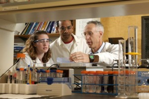 David Grant, right, associate professor of pharmaceutical science, with students, in his lab.