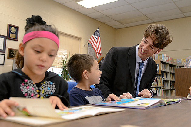 Michael Coyne, associate professor of educational psychology, reads with a group of first, second and third graders at the Windham Center School on Oct. 11, 2012. (Peter Morenus/UConn Photo)