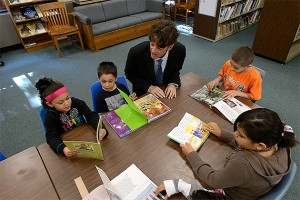 Michael Coyne, associate professor of educational psychology, reads with a group of first, second and third graders at the Windham Center School (Peter Morenus/UConn Photo)