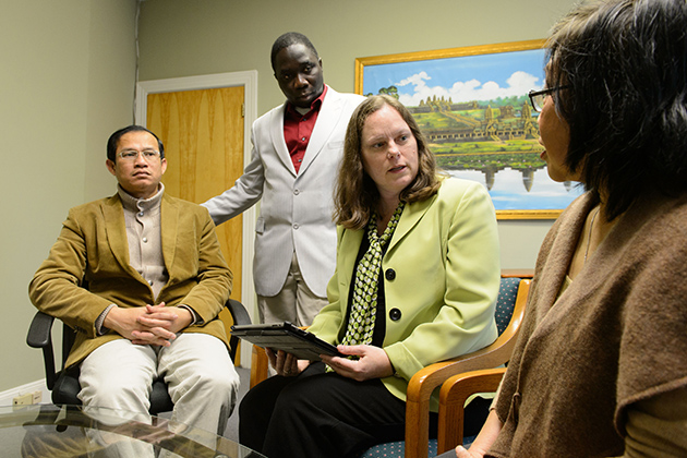 Megan Berthold, assistant professor of social work, meets with Theanvy Kuoch, executive director, right, Sengly Kong, co-investigator, left, and Gabriel Babalola, financial manager, at Khmer Health Advocates in West Hartford on Dec. 18, 2012. (Peter Morenus/UConn Photo)