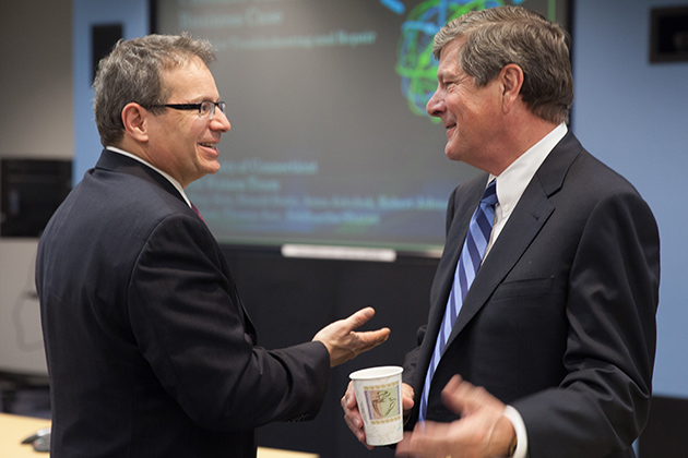 Stephen Gold (left), worldwide marketing director for IBM's Watson Solutions, talks with UConn School of Business Dean John Elliott after a presentation by student teams from UConn's Stamford Learning Accelerator. (Zach Wussow for UConn)