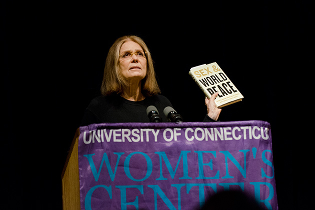 Gloria Steinem holds up a recently published book that examines the treatment of women in society in relation to the incidence of conflict and war, during a public lecture in the Student Union Theatre on Nov. 30. (Ariel Dowski '14 (CLAS)/UConn Photo)