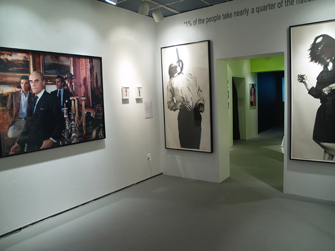 'Father & Son, 1996' by Tina Barney, left, and two lithographs by Robert Longo depicting a well-dressed man and woman seeming to fall away from the viewer, are on display as part of the Gatsby Revisited in the Age of the One Percent exhibition. (Photo courtesy of CAG)