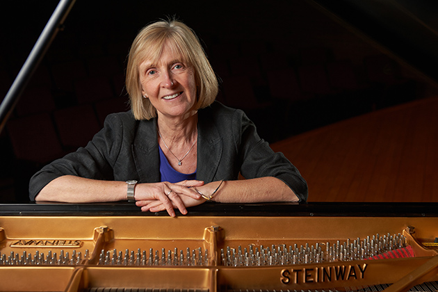 Brid Grant, dean of fine arts, sits at a Steinway grand piano on the stage of von der Mehden Recital Hall on April 2, 2013. (Peter Morenus/UConn Photo)