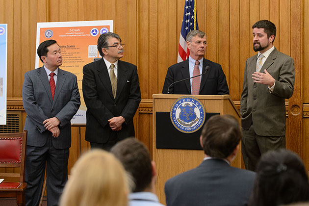 Eric Jackson, right, assistant research professor and director of the Connecticut Transportation Safety Research Center, speaks at the press conference. From left are UConn Provost Mun Choi, Kazem Kazerounian, interim dean of engineering, and James P. Redeker, commissioner of the Connecticut Department of Transportation. (Peter Morenus/UConn Photo)