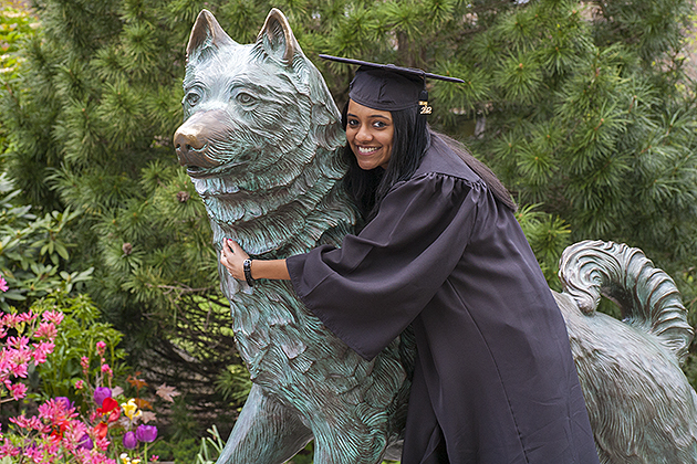 2012 graduates of the University of Connecticut pose for pictures near Jonathan the husky dog statue on May 6, 2012. (Sean Flynn/UConn Photo)