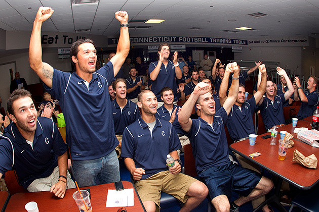 The baseball team, led by LJ Mazilli (standing), finds out that it will play in the Blacksburg, Va. Regional in the NCAA tournament. (Steve Slade '89 (SFA) for UConn)