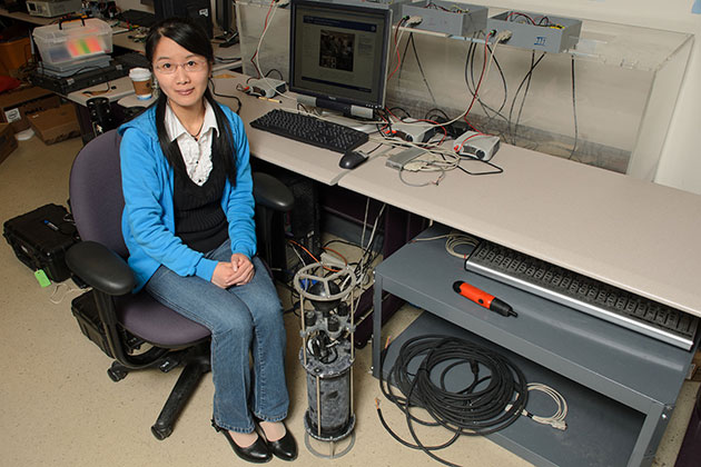 Zhaohui Wang, a Ph.D. candidate in engineering, sits in a lab next to the OFDM underwater modem on April 30, 2013. (Ariel Dowski/UConn Photo)