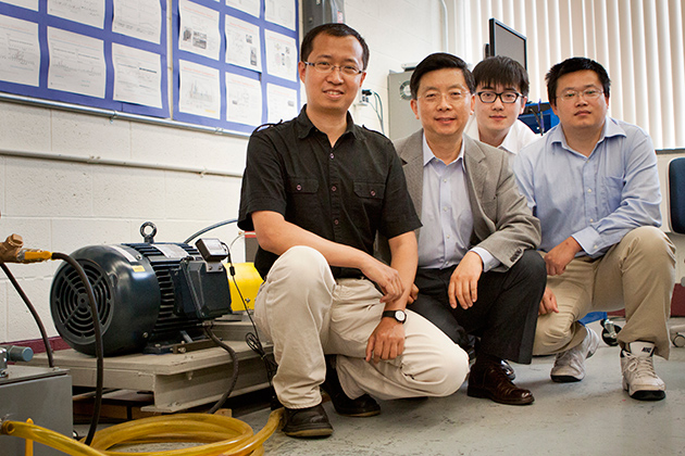 Pratt & Whitney Chair professor Robert Gao, second from left, with (left to right) Zhaoyan Fan, assistant research professor of mechanical engineering, and Ph.D. students Peng Wang and Jinjiang Wang, with a drivetrain prognostic simulator. (Chris LaRosa/UConn Photo)