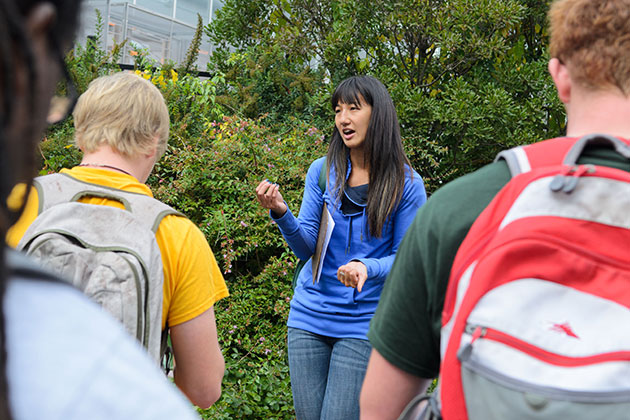 Students observe different trees, shrubs, and vines during a walk around campus with teaching assistant Thao Hau, a graduate student in the College of Agriculture and Natural Resources, as part of Professor Mark Brand's horticulture class on Woody Landscape Plants. (Ariel Dowski '14 (CLAS)/UConn Photo)