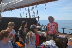 The Mystic Whaler's first mate (in tye-die shirt) addresses the students. (Nathaniel Trumbull/UConn Photo)