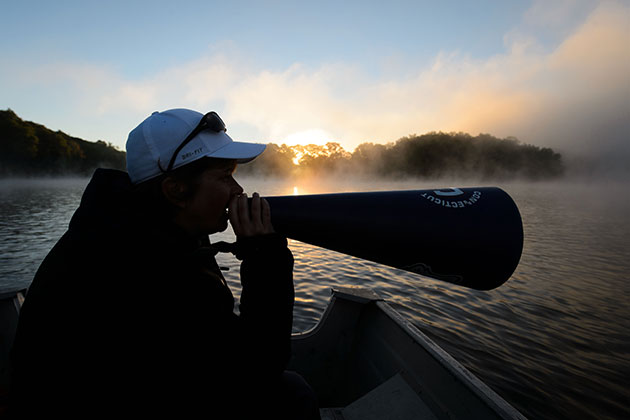 Head Coach Jennifer Sanford-Wendry uses a megaphone to give directions to UConn Rowing team members on Coventry Lake on Sept. 18, 2013. (Peter Morenus/UConn Photo)