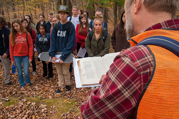Robert Thorson, professor of geology, reading passages of Thomas Cole and Thoreau to a group of students during a field trip to Tift Pond in the Albert E. Moss Sanctuary. (Sean Flynn/UConn Photo)
