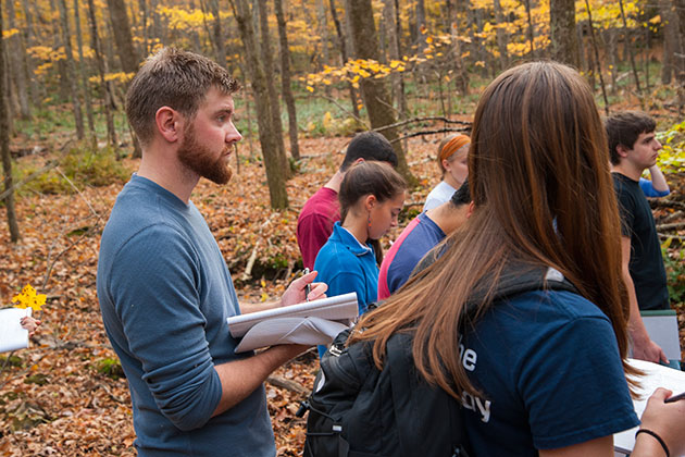 Students listen to Robert Thorson, professor of geology, teaching a class outdoors along the Fenton River. (Sean Flynn/UConn Photo)