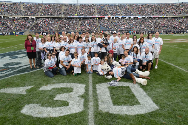 "Members of the Stamos/Heerdt/Vartelas/Vlandis family pose for UConn's ""Biggest UConn Family"" portrait at Rentschler Field on Saturday, Oct. 12, 2013. Almost 60 family members received an exclusive Homecoming package, including tickets to the game, admission to the Alumni Association BBQ, T-shirts, and on-field recognition. (Peter Morenus/UConn Photo)"