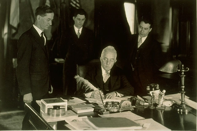 Gov. Wilbur Cross, center, signs the bill that made Connecticut Agricultural College the Connecticut State College in 1933.
