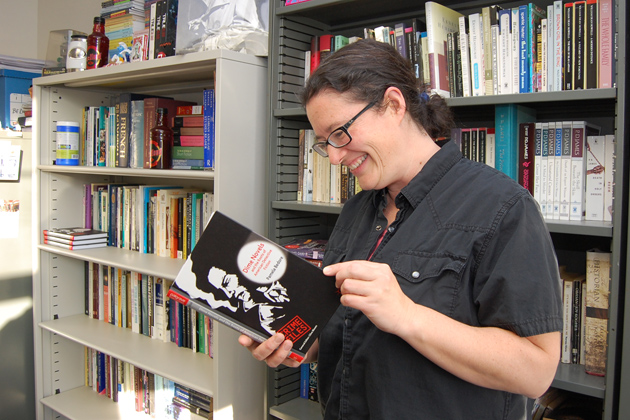 Pamela Bedore, assistant professor of English at the Avery Point campus, with her new book, Dime Novels and the Roots of American Detective Fiction, which traces the influence of 19th-century dime novels on writers such as Mark Twain, William Faulkner, Dashiell Hammett, and Raymond Chandler. (Ken Best/UConn Photo)