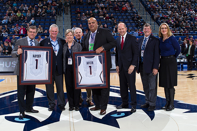 Alumni Denis and Britta Nayden, second and third from left, were honored for their $3 million commitment to the UConn basketball program during the women's game at the XL Center on Dec. 5. From left: Coach Geno Auriemma, Denis Nayden, Britta Nayden, UConn Board of Trustees Chairman Lawrence McHugh, Director of Athletics Warde Manuel, President of the UConn Foundation Joshua Newton, School of Business Dean John Elliott, and SNY analyst and former UConn Husky Meghan Pattyson-Culmo. (UConn Foundation Photo)