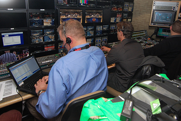 The wall of 54 monitors in the ESPN GameDay production truck, with Doug Holmes, the director, in the blue shirt. (Ken Best/UConn Photo)