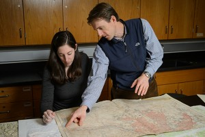Will Ouimet, assistant professor of geography, and Katharine Johnson, a PhD. student, look over old maps of New England. (Peter Morenus/UConn Photo)