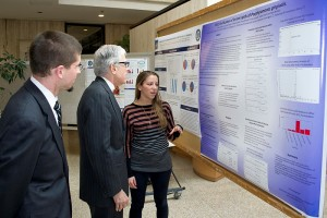 Emily Anstadt explains her poster to Dr. Barry Coller and M.D.-Ph.D. student Alex Adami. (Chris Defrancesco/UConn Health Photo)
