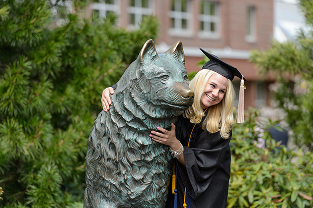 Chelsea McCallum of Somers poses for a photo with Jonathan statue following the School of Business commencement ceremony at Harry A. Gampel Pavilion on May 12, 2013. (Peter Morenus/UConn Photo)
