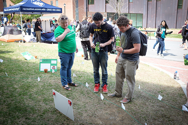 """Sophie Marking '16 (CLAS), left, helps Thomas Chadwick '17 (CLAS) and Paul Ference '17 (ENG) determine their carbon """"pawprint"""" as they navigate a maze during the UConn Earth Day Spring Fling held along Fairfield Way on April 22, 2014. (Peter Morenus/UConn Photo)"""