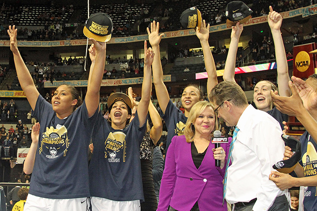 From left Kaleena Mosqueda-Lewis '15 (CLAS), Bria Hartley '14 (CLAS), Kiah Stokes '15 (CLAS), and Breanna Stewart '16 (CLAS) celebrate the team's championship win in Nashville, Tenn., while head coach Geno Auriemma is interviewed for ESPN. (Bob Stowell '70 (CLAS) for UConn)