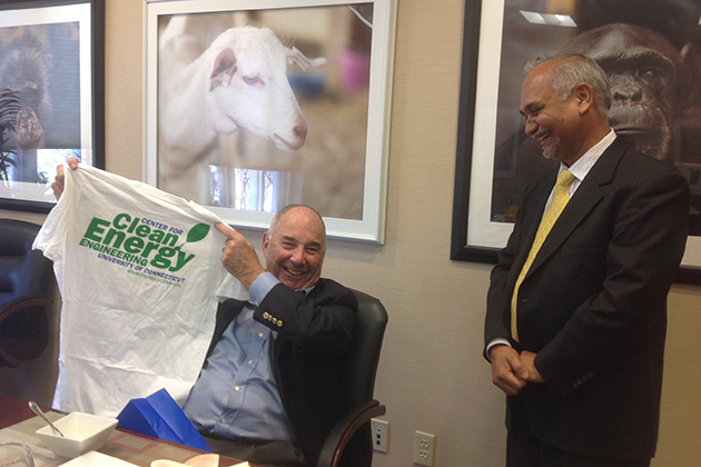 Ed Satell '57 (BUS), left, displays a T-shirt given to him by Prabhakar Singh, director of the Center for Clean Energy Engineering, in the President's conference room at Gulley Hall, during a recent visit to the Storrs campus. (UConn Foundation Photo)
