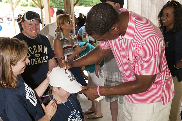Kevin Ollie, head coach of UConn men's basketball, signs the cap of a young fan during Cancer Survivors Day recently. (Lou Russo Photography for UConn)